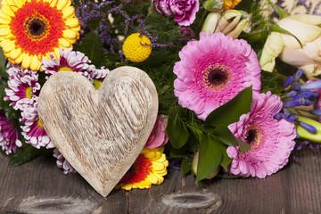 Rustikales Holzherz vor einem Blumenstrauß auf Holztisch