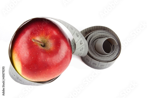 Measuring tape wrapped around a red apple on white.