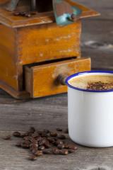 Kaffeebecher und Kaffeebohnen mit Mühle