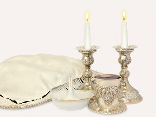 Jewish Sabbath objects.Candles,wine cup, covered challah,salt.