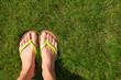 Closeup of bright flip flops and legs on green grass