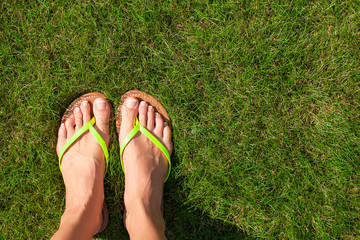 Closeup of bright flip flops and legs on green grass