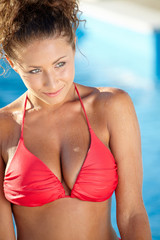 Gorgeous woman in a red bikini standing in the water at the edge