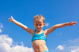 Adorable little girl spread her arms background of the blue sky