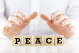 Man holding protective hands above the word Peace