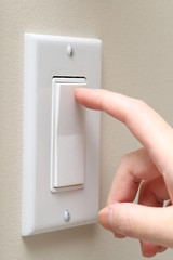 Woman hand turning on the light with a wall switch