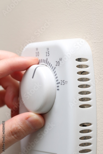Woman hand setting a thermostat