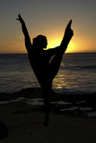 Siljouette of a woman doing yoga at the beach during sunset