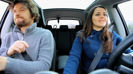 Couple having fun dancing in the car while driving