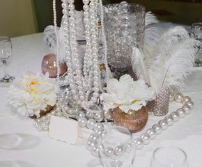 Table decorated with feathers, pearls and candles