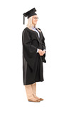 Full length portrait of young woman in graduation gown