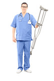 Male healthcare professional holding a pair of crutches