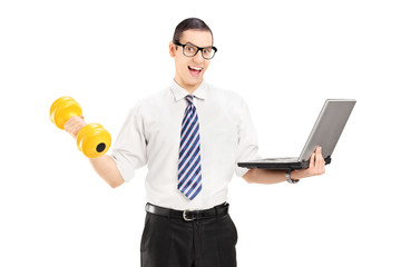 Young businessman holding dumbbell and laptop