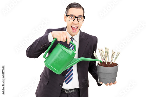 Young businessman watering money in a flowerpot