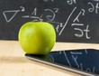 digital tablet pc and green apple in front of blackboard