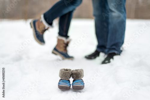 detail of baby boots and expecting couple enjoying a snowy day