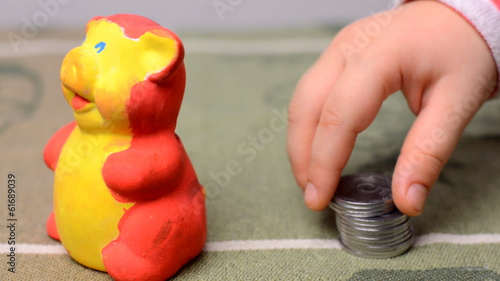Little Baby Putting Coins into Moneybox