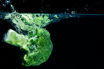 Green broccoli falling in water