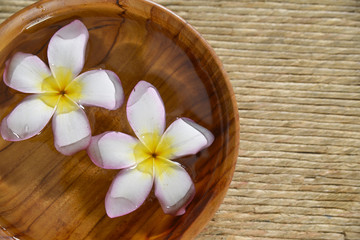 frangipani flower in wooden bowl on Brown straw mat