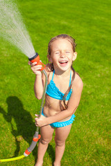 Happy cute little girl pouring water from a hose and laughing