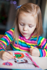 Little cute girl painting with pencils while sitting at her