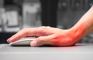 Hand holding computer mouse having wrist pain