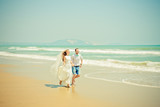 Bride and groom running on the beach