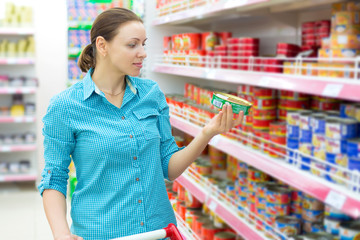 A woman buys tinned meat