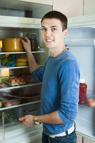 Man looking for something in pan near fridge
