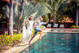 bride and groom jumping in the pool