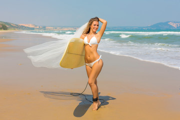 Beautiful sexy surfer girl in bikini on the beach