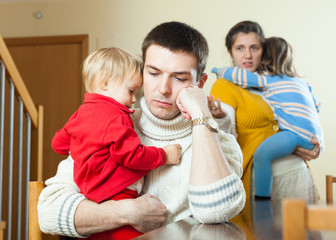 Ordinary young sad  family of four after quarrel