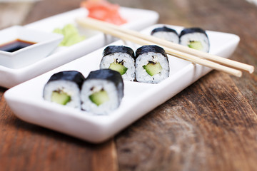 Chopsticks on a set of cucumber sushi