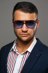 Fierce successful man in violet sunglasses