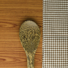 kitchen towel with spoon on wood background