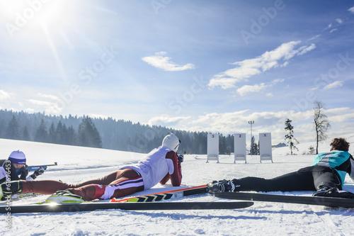 Foto op Plexiglas Wintersporten Drei Biathleten beim Schießen