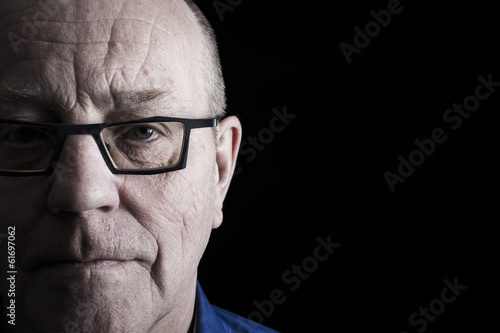 Closeup portrait of older man on black background.