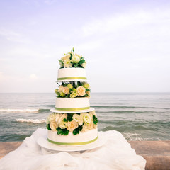 White and roses wedding cake by the beach