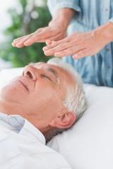 Senior man having Reiki treatment