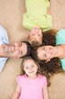 Smiling family lying on the rug in a circle