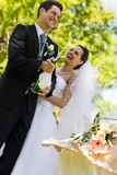 Newlywed couple with groom opening champagne bottle at park