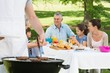 Barbecue grill with extended family having lunch in park