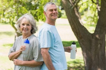 Mature couple standing with water bottles at park