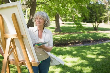 Mature woman painting in park