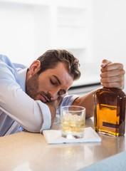 Drunk businessman clutching whiskey bottle asleep