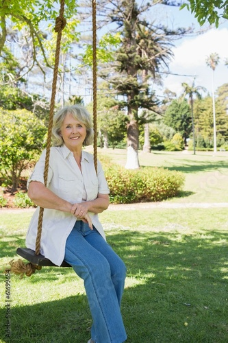 Smiling mature woman sitting on swing in park