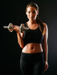 Woman lifting a dumbbell over dark background