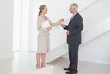 Smiling estate agent handing over keys to customer