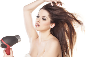 young woman dries her hair on white background