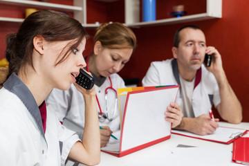 Drei Pfleger beim Telefonieren und Daten notieren